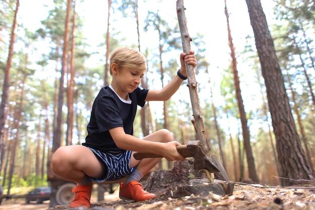 Il ragazzo tiene un'ascia in una mano e un bastone nell'altra e la taglia per la legna da ardere