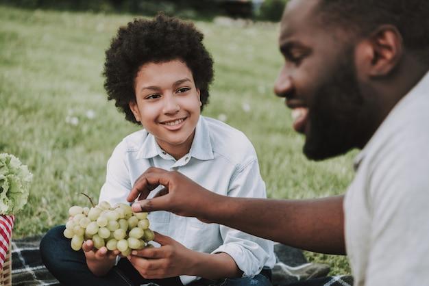 Il ragazzo tiene l'uva e il padre allunga per provare.