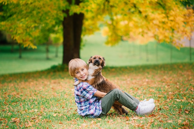Ragazzo che abbraccia un cane e gioca con in autunno, parco cittadino