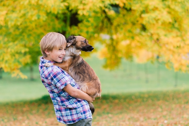 Ragazzo che abbraccia un cane e plyaing con in autunno, parco cittadino