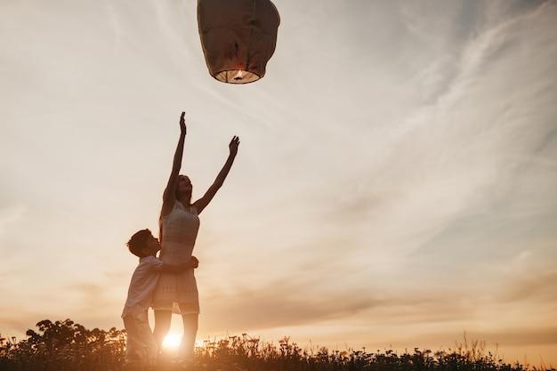 Ragazzo che abbraccia la sorella teenager durante il lancio della lanterna del cielo