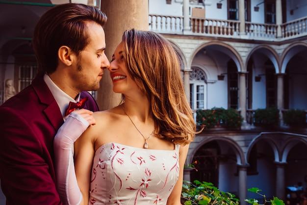 Il ragazzo abbraccia la sua ragazza tra una varietà di dipinti e architettura