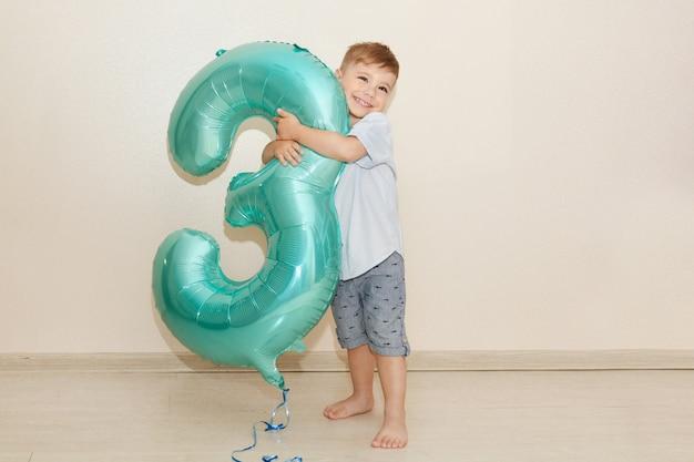 Il ragazzo abbraccia il numero tre per il suo compleanno