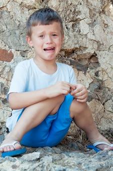 Il ragazzo sta piangendo, cattivo. il bambino sperimenta brutte emozioni e frustrazione