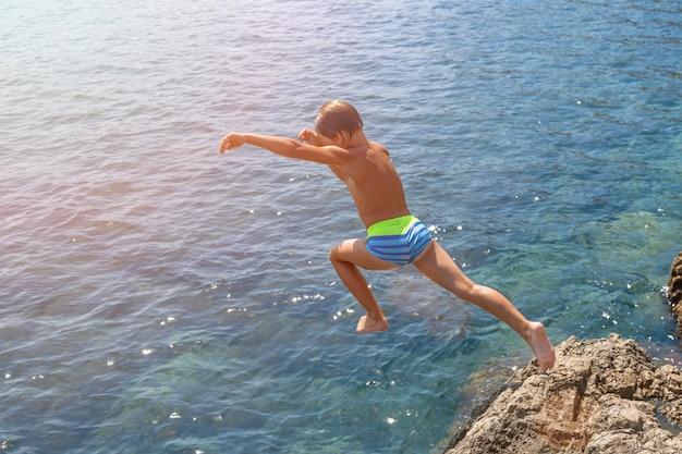 Un ragazzo sta saltando dalla scogliera verso il mare in una calda giornata estiva. vacanze al mare. il concetto di turismo attivo e ricreazione