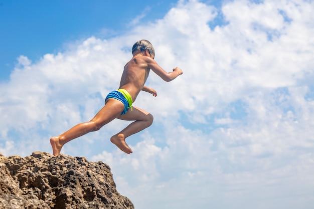 Un ragazzo sta saltando dalla scogliera in mare in una calda giornata estiva. vacanze in spiaggia. il concetto di turismo attivo e ricreazione