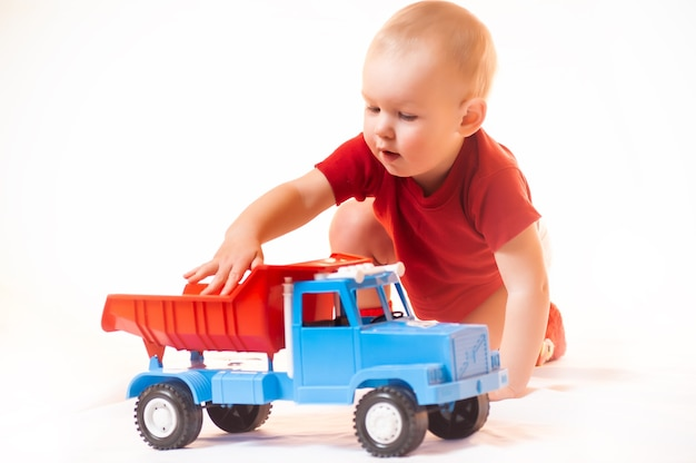 Un ragazzo si gioca con le macchinine in un ambiente domestico naturale e semplice. il concetto di uno stile di vita attivo e sano di un bambino.