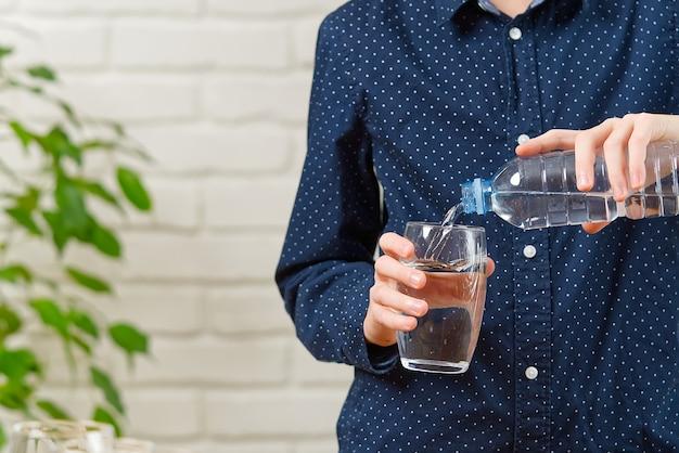 Ragazzo sta versando l'acqua dalla bottiglia di plastica nel bicchiere sul tavolo di legno