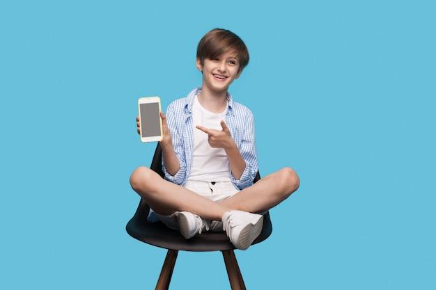Il ragazzo è seduto su una poltrona e sta indicando il suo schermo del telefono sorridendo