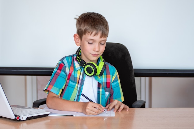 Un ragazzo è seduto al tavolo, scrive, si prepara per un esame