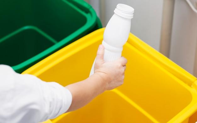 Il bambino getta la bottiglia di plastica vuota in uno dei tre bidoni della spazzatura
