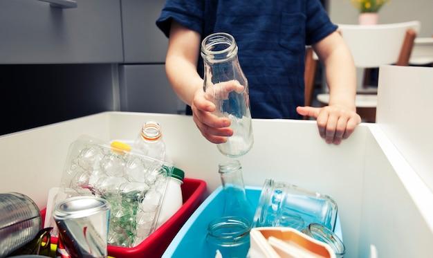 Il ragazzo getta la spazzatura di vetro in uno di quattro diversi bidoni per lo smistamento della spazzatura.
