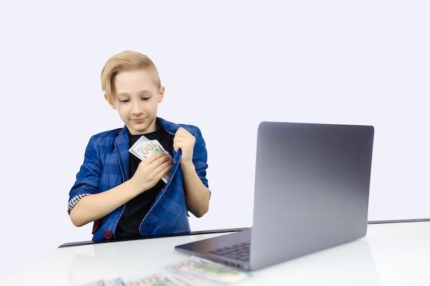 Il ragazzo in una giacca dietro un laptop nasconde i soldi nella sua tasca interna