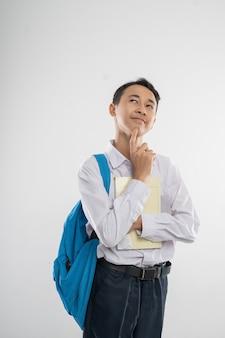 Un ragazzo in uniforme della scuola media che sorride guardando in alto quando pensa al gesto quando tiene in mano un libro e...