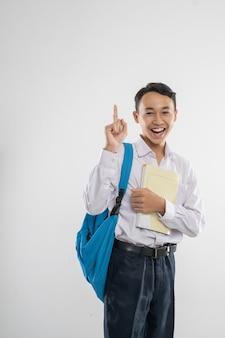 Un ragazzo in uniforme della scuola media che sorride con il dito puntato mentre porta un libro e uno zaino...