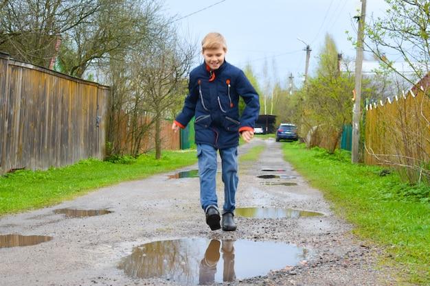 Ragazzo bambino che salta in una pozza di fango