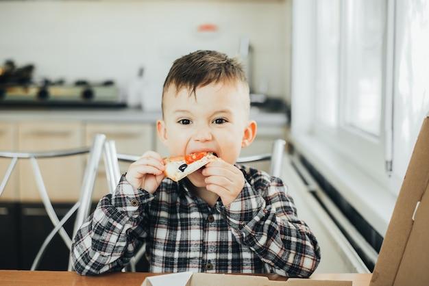 Il ragazzo in cucina a casa che mangia pizza con salmone