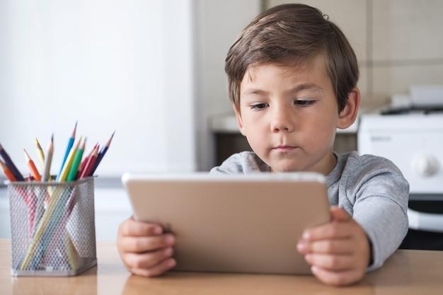 Un ragazzo in cucina guarda un video su un tablet durante la pandemia covid-19.