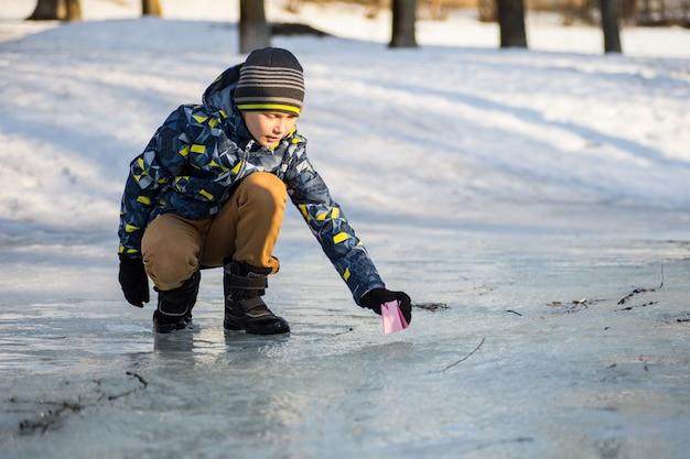 Un ragazzo lancia una barchetta di carta nel torrente primaverile Foto Premium