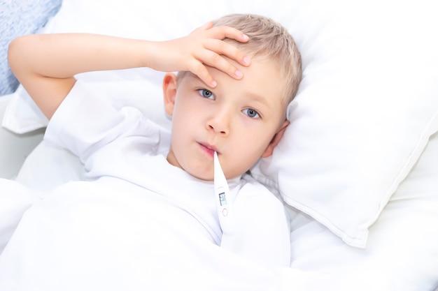 Ragazzo giace a letto con un termometro in bocca. concetto sanitario e bambino malato, coronavirus, febbre alta,