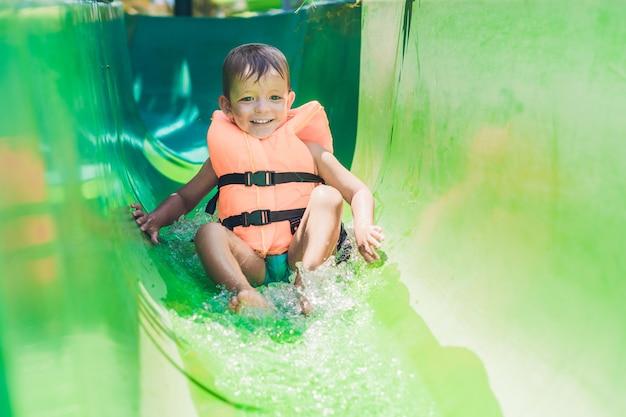 Un ragazzo con un giubbotto di salvataggio scivola giù da uno scivolo in un parco acquatico.