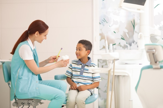 Ragazzo in ascolto. ragazzo allegro dalla pelle scura che ascolta il dentista che racconta di lavarsi i denti