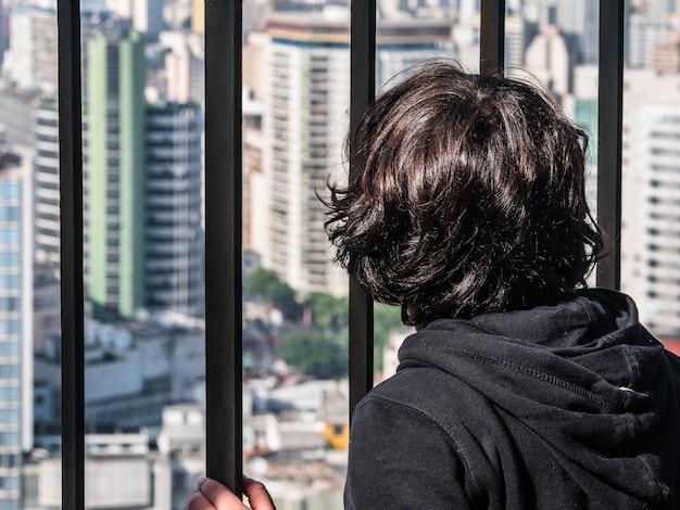 Ragazzo che guarda alla città dietro le sbarre.
