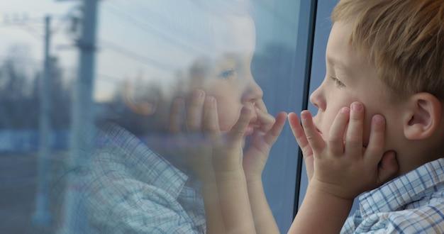 Ragazzo che guarda fuori dal finestrino del treno con le mani sul viso