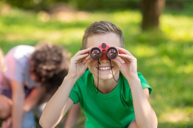 Ragazzo che guarda attraverso il binocolo in natura