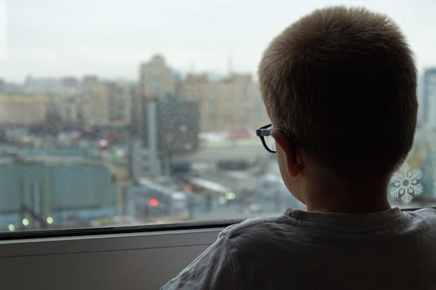 Il ragazzo guarda fuori dalla finestra auto isolamento una nuova realtà una nuova normalità