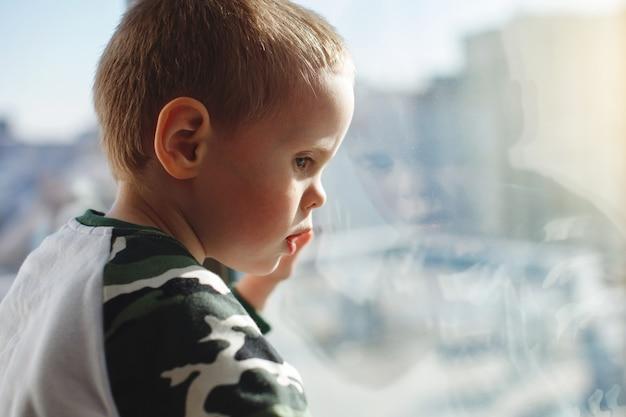 Il ragazzo guarda fuori dalla finestra in una giornata invernale