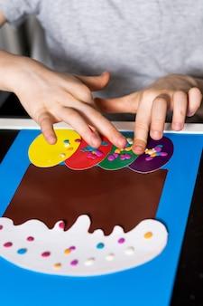 Il ragazzo fa un biglietto di pasqua con le sue mani una torta di pasqua e uova di pasqua di carta
