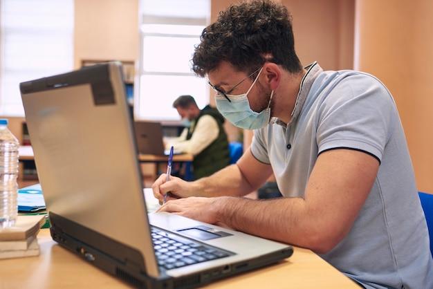 Un ragazzo con una maschera sta studiando con un computer portatile in biblioteca