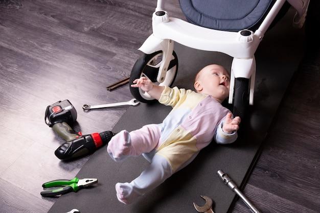 Il meccanico del ragazzo ripara la sospensione di una carrozzina. ripariamo tutto ciò che viaggia. umorismo, sfida.