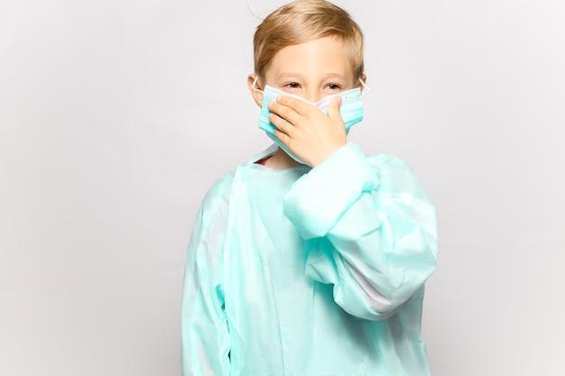 Un ragazzo in un abito medico regola la maschera medica che viene indossata sul viso