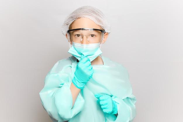Un ragazzo in camice e maschera medica regola la maschera con la mano che indossa guanti monouso