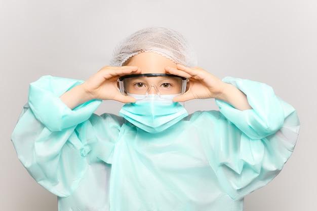 Un ragazzo in abito medico e maschera tiene in mano occhiali protettivi e guarda la telecamera. un bambino travestito da medico