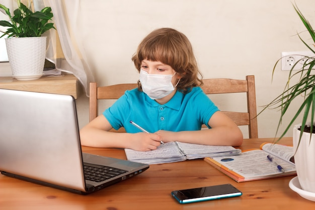 Ragazzo in maschera medica sul viso facendo i compiti e guardando webinar al computer portatile. formazione a distanza, homeschooling, e-learning a casa durante il concetto di quarantena