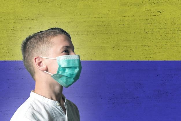 Ragazzo in una mascherina medica sul suo viso su sfondo di bandiera ucraina.