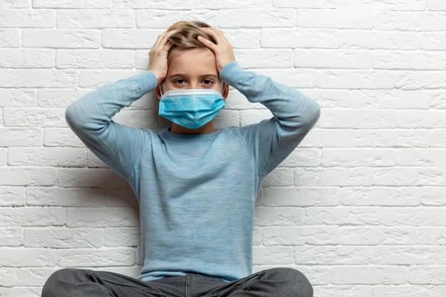 Un ragazzo con una maschera medica gli tiene la testa con le mani. un bambino di 9 anni con un maglione blu.