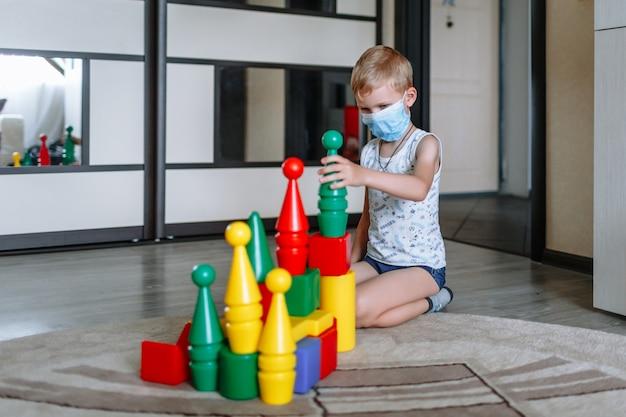 Un ragazzo in una mascherina medica che gioca con le figure colorate a casa