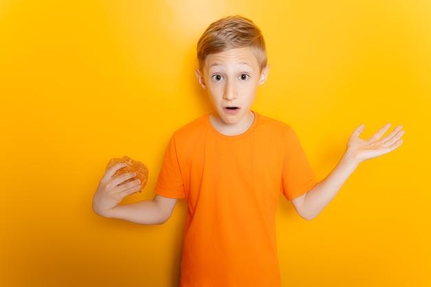 Un ragazzo con una maglietta arancione tiene un hamburger in una mano allarga le braccia ai lati e mostra un gesto di smarrimento