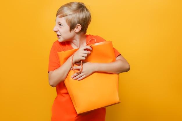 Un ragazzo con una maglietta arancione tiene un pacco con entrambe le mani che lo stringono al petto ed è arrabbiato