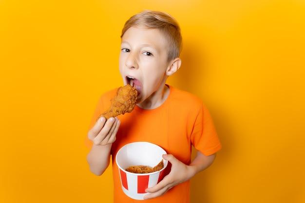 Un ragazzo con una maglietta arancione tiene davanti a sé un secchio di carta con ali di pollo e nell'altra tiene una coscia di pollo impanata e la morde