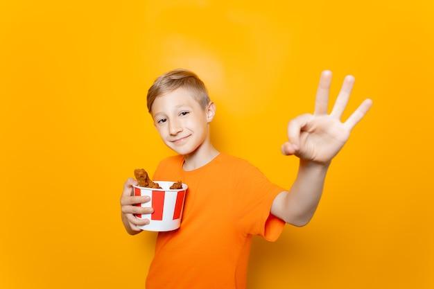 Un ragazzo con una maglietta arancione tiene davanti a sé un secchio di carta con ali di pollo e mostra il segno ok
