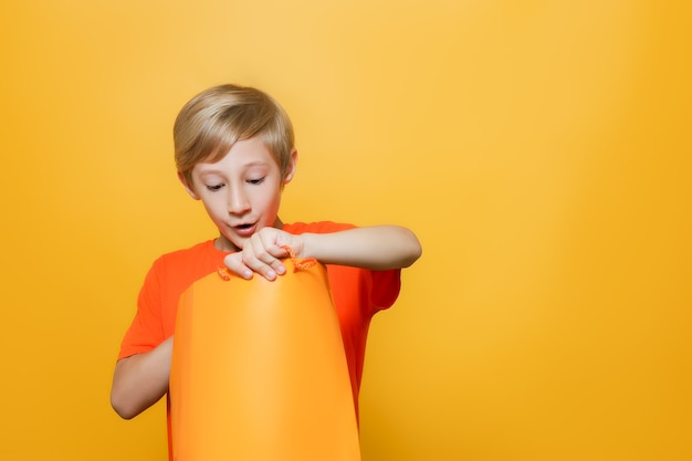 Un ragazzo con una maglietta arancione e su uno sfondo giallo tiene in mano una borsa della spesa lo guarda con sorpresa
