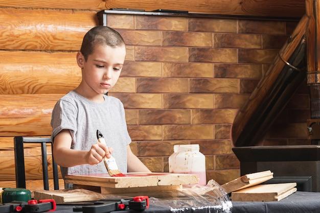 Un ragazzo dipinge una finta di legno con un pennello in rosso in una casa di campagna