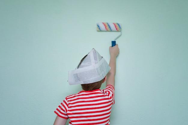Ragazzo con un cappello di carta dipinge il muro con un rullo