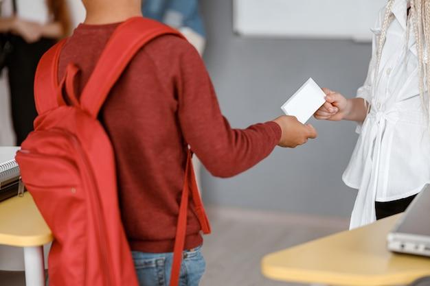 Ragazzo che passa una nota di carta a una ragazza a scuola