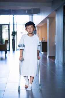 Ragazzo paziente che cammina con le stampelle in corridoio